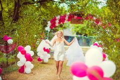Beautiful bride in silk dressing gown running barefoot to her wedding dress, free space. Wedding morning preparation in sunny summ. Er day, pink and white royalty free stock photos