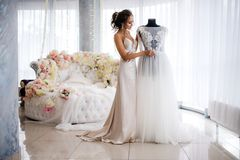 A beautiful bride in a silk night dress admires her wedding dress in the boudoir room. Large white bed decorated with flowers on the background. Wedding Stock Photography