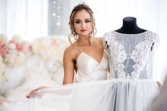 A beautiful bride in a silk night dress shows her wedding dress in the boudoir room. White bed decorated with flowers on the background Stock Photo