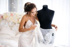 A beautiful bride in a silk night dress takes off her wedding dress from the dummy in the boudoir room. White bed decorated with flowers on the background Stock Photo