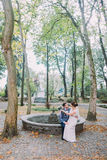 Beautiful bride in silk wedding gown sitting on knees of her loving groom while he rest by the dried fountain in green Royalty Free Stock Images