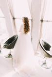 Beautiful bride in silk white dress standing next to sunlit window near two modern chairs Royalty Free Stock Images