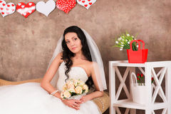 Beautiful bride sits with a bouquet Royalty Free Stock Photography