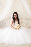 Beautiful bride sits with a bouquet Stock Image