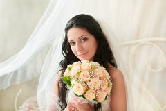 Beautiful bride sits with a bouquet Stock Images