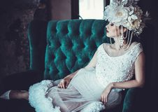 Beautiful bride sits on a chair. Luxury palace. Beautiful young bride sits on a chair. Luxury palace royalty free stock photo