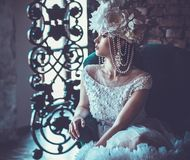 Beautiful bride sits on a chair. Luxury palace. Beautiful young bride sits on a chair. Luxury palace stock images