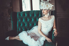 Beautiful bride sits on a chair. Luxury palace. Royalty Free Stock Photography