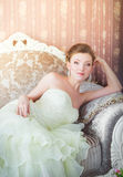Beautiful bride sits on the couch. The bride sits in a wedding dress on the sofa in the interior Stock Photography
