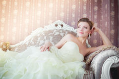 Beautiful bride sits on the couch. The bride sits in a wedding dress on the sofa in the interior Royalty Free Stock Photo
