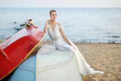 Beautiful bride sitting on a boat Stock Photo