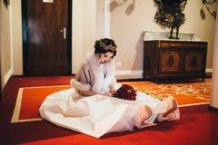 Beautiful bride sitting on the floor Stock Photos