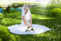 Beautiful bride sitting on grass Royalty Free Stock Photography