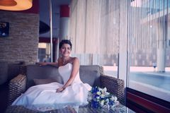 Beautiful bride sitting at an indoor cafe Stock Images