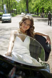 Beautiful bride sitting on a motorcycle. Beautiful young bride sitting on a motorcycle and playfully looks into the camera stock photo