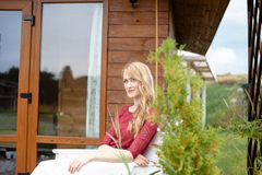 Beautiful bride sitting next to the wooden house Royalty Free Stock Photos