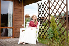 Beautiful bride sitting next to the wooden house Stock Images