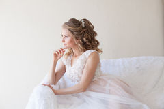 Beautiful bride sitting on a white couch in lingerie Stock Image