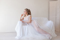 Beautiful bride sitting on a white couch in lingerie Stock Images