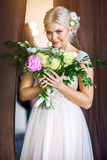 Beautiful bride smelling bouquet of flowers. In the Studio Stock Photos