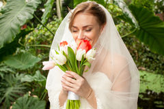 Beautiful bride smelling bridal bouquet Stock Images