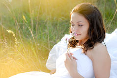 Beautiful bride smelling flower lying outdoors Stock Images