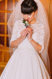 Beautiful bride smells cute floral boutonniere in dressing room before wedding.  royalty free stock image