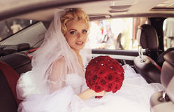 Beautiful bride smile in a luxury car with red ros Royalty Free Stock Photo