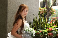 Beautiful bride smiles, looking off camera. Beautiful caucasian redhead bride with bouquet of flowers smiles with her hair flowing over one shoulder Royalty Free Stock Photography