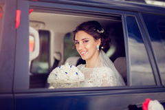 Beautiful bride smiling from the car window Royalty Free Stock Image