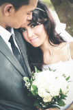 Beautiful bride smiling while lean on her groom shoulder Royalty Free Stock Images