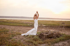 Beautiful bride smiling and posing near the dead tree in a field Stock Images