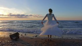 Beautiful bride spinning around on beach in sunset. Wonderful seascape background. Super slow motion footage stock footage