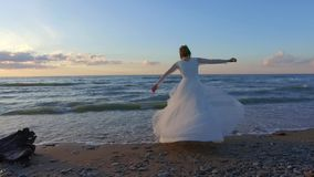 Beautiful bride spinning around on beach in sunset. Wonderful seascape background. Super slow motion footage stock video footage