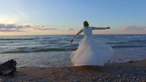Beautiful bride spinning around on beach in sunset. stock video footage