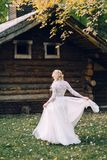 The Beautiful bride is spinning around herself in fluttering dress on wooden house background. Back view. Artwork. The Beautiful bride is spinning around herself royalty free stock photography