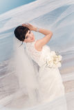 Beautiful bride standing by the beach Stock Photo