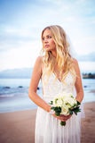 Beautiful bride standing by the beach at sunset Royalty Free Stock Photography