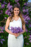 Beautiful bride standing with flowers near blooming lilac tree Stock Photography