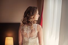 Beautiful bride standing in her bedroom and looking in window Royalty Free Stock Photos