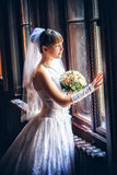 Beautiful bride standing near the window Stock Images