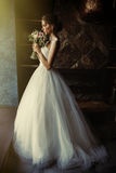 A beautiful bride is standing in a room in the window of a window. A beautiful bride stands in a room in the window`s window and holds flowers in her hands Royalty Free Stock Images