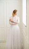 Beautiful bride standing at window Royalty Free Stock Image