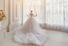 Beautiful bride with a long train, standing at the window. Beautiful bride, standing at the window Stock Photo