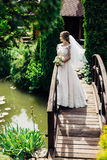 The beautiful bride. Beautiful bride is standing on a wooden bridge Royalty Free Stock Photography