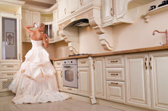Beautiful bride stands in the kitchen Royalty Free Stock Images