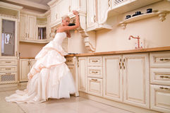 Beautiful bride stands in the kitchen Stock Images