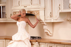 Beautiful bride stands in the kitchen Royalty Free Stock Photography