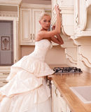 Beautiful bride stands in the kitchen Stock Photo