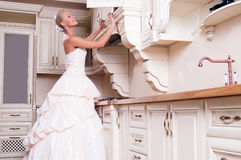 Beautiful bride stands in the kitchen Royalty Free Stock Photos